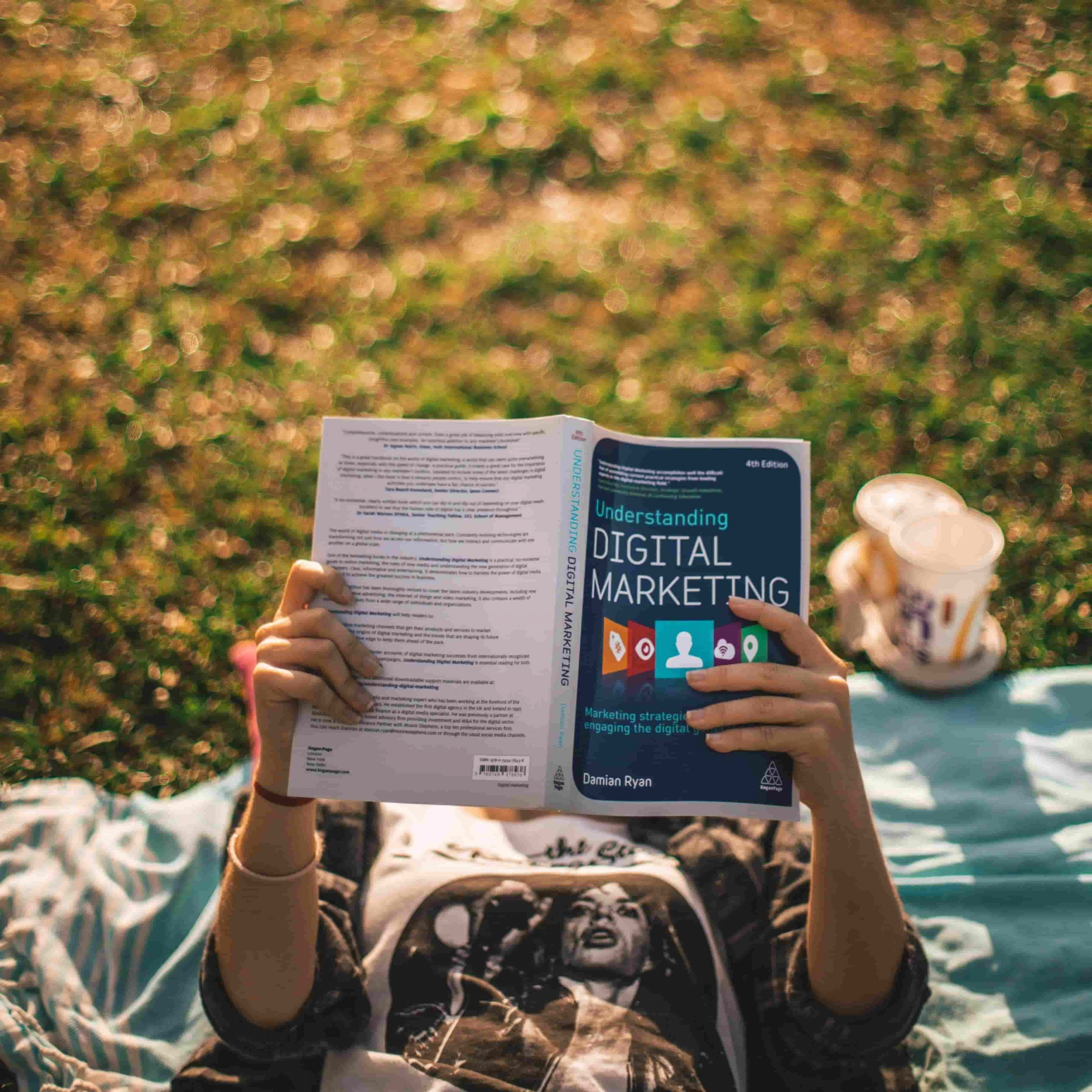 Person lying in the grass reading a marketing book